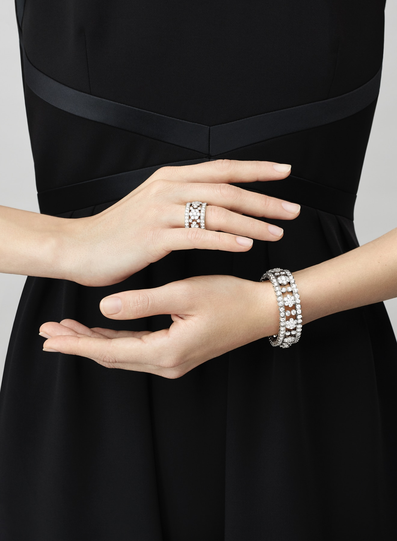 Diamond sets collection, ring and bracelet, white gold and diamonds, hand hovering in front of waist, Van Cleef & Arpels