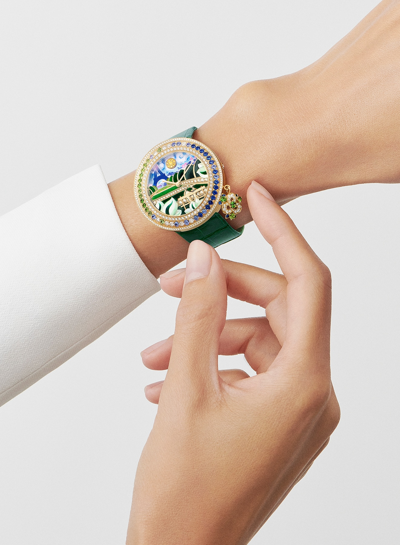 Extraordinary Dials collection, watch, yellow gold, tsavorite, diamonds, mother-of-pearl and sapphire, hand trying to catch charm, Van Cleef & Arpels